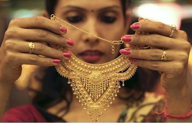 A salesgirl shows a gold necklace to customers at a jewellery showroom in Chandigarh