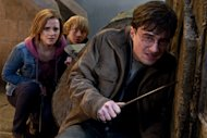 "In this film publicity image released by Warner Bros. Pictures, from left, Emma Watson, Rupert Grint and Daniel Radcliffe are shown in a scene from ""Harry Potter and the Deathly Hallows: Part 2."" The movie pulled in $21.9 million to become the franchise's top-grossing chapter at $318.5 million domestically. (AP Photo/Warner Bros. Pictures, Jaap Buitendijk)"