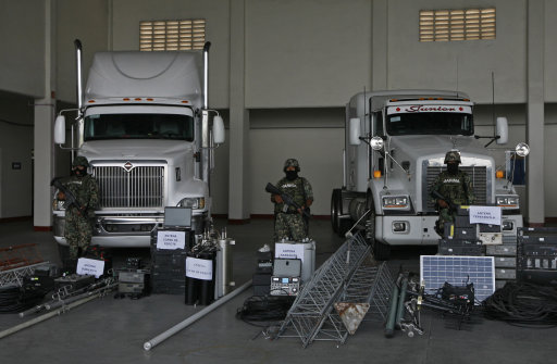 Members of the Mexican Navy stand guard over seized telecommunications equipment, allegedly built by the Zetas drug cartel, during a media presentation in Veracruz, Mexico, Thursday Sept. 8, 2011. The Mexican Navy says it has dismantled a telecommunications system set up by the cartel and has arrested 80 people, including six policemen. (AP Photo/Marco Ugarte)