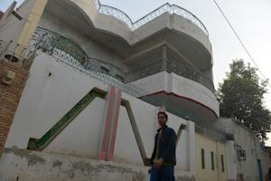 A local resident walks past the house of Gulzar Ahmed …