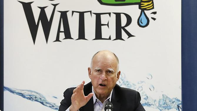FILE- In this April 16, 2015 file photo, California Gov. Jerry Brown talks with reporters after a meeting about the drought at his Capitol office in Sacramento, Calif. The State Water Resources Control Board is considering sweeping mandatory emergency regulations to protect water supplies as water levels as some of California's lakes and reservoirs continue to decline. Brown has argued that the voluntary targets in place since early 2014 were insufficient and that Californians needed a jolt to take conservation seriously. (AP Photo/Rich Pedroncelli, File)