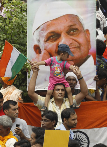 A supporter of anti-corruption activist Anna Hazare, portrait seen, carries a child on his head as he waits along with others outside Tihar prison, where Hazare is presently lodged, in New Delhi, India, Thursday, Aug. 18, 2011. The renowned Indian anti-corruption crusader struck a deal with police Thursday to hold a 15-day public hunger strike against graft, ending a standoff at a New Delhi prison in which he turned his brief detention into a sit-in protest. (AP Photo/Pankaj Nangia)