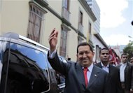 Hugo Chavez waves to supporters as he arrives at the Simon Bolivar house to mark the birthday of the independence hero in Caracas