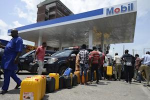 People queue with jerrycans to buy fuel at Mobil filling …