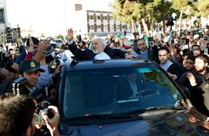 Iranian Foreign Minister Mohammad Javad Zarif (C) gets…