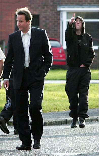 "FILE -- In this Feb. 22, 2007 file photo, Conservative Party leader David Cameron walks through the Benchill area of Wythenshawe, England, whilst Ryan Florence, 17, makes a gun gesture. It wasn't so long ago that David Cameron launched his ""Hug a Hoodie"" campaign - an intiative born out of public outcry over Britain's feral youths, and one that ended in ridicule when hooded youths mocked the then-Conservative leader during a photo opportunity. Now, Prime Minister Cameron is opting for tough love in the wake of Britain's riots but critics say it may be too little too late. (AP Photo/Martin Rickett-pa, file) UNITED KINGDOM OUT: NO SALES: NO ARCHIVE:"