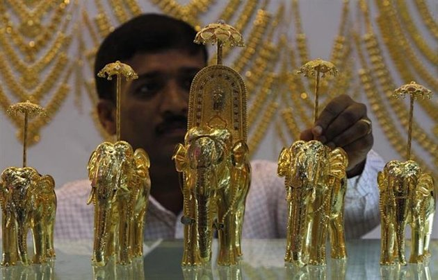 An employee displays gold models of elephants at the