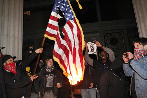 Occupy Oakland protestors burn an American flag found inside Oakland City Hall during an Occupy Oakland protest on the steps of City Hall, Saturday, January 28, 2012, in Oakland, Calif.  (AP Photo/Beck Diefenbach)