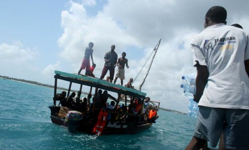 Deck hands aboard the tourist diving vessel Kisi throw bottles of water to the parched survivors of the Zanzibar ferry that sunk off the coast of Pemba overnight