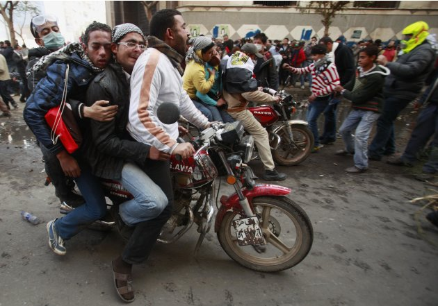 Wounded protesters are evacuated on motorbikes during clashes with security forces near the Interior Ministry in Cairo