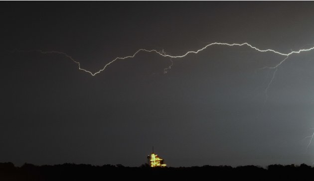 Lightning flashes in the sky above space shuttle Endeavour at the Kennedy Space Center on Cape Canaveral, Fla.,  Thursday, April 28, 2011.  Endeavour is scheduled to launch Friday afternoon on its las