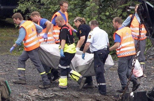Rescue workers unload the body of a victim from a ferry boat at the lake shore opposite the island of Utoya (AP)