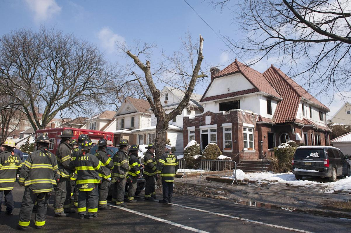 Firefighters stand outside a home hours after it caught fire in the Midwood neighborhood of Brooklyn, New York