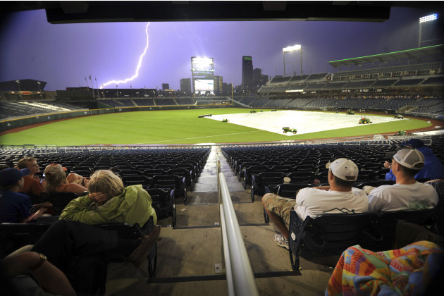 A lightning bolt strikes in the distance as spectators wait for the storm to blow over at TD Ameritrade Park in downtown Omaha, Neb., Monday, June 20, 2011, where Vanderbilt and Florida were playing i
