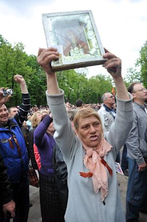 A woman holds a Christian Orthodox icon of the Virgin …