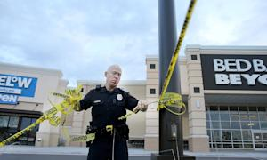A Waco police officer takes down crime scene tape,…