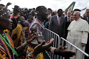 Pope Francis is greeted by traditional dancers at Jommo …
