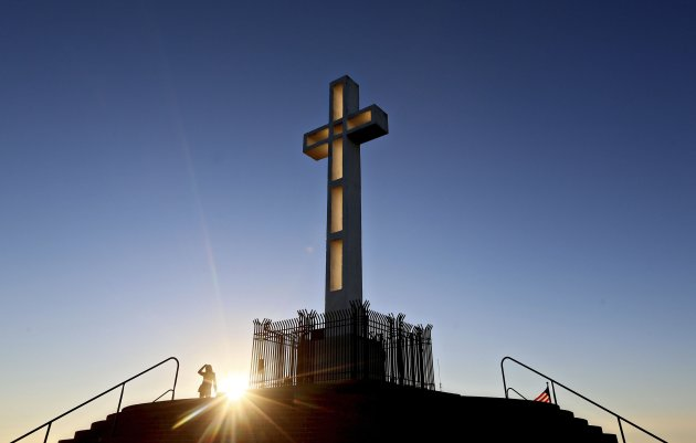 People gather in the late evening sun around the massive cross sitting atop the Mt. Soledad War Memorial in La Jolla, California on December 12, 2013. A federal judge has ruled that the cross is an unconstitutional religious display on government land and must come down within 90 days. The decision could result in the case being sent back to the U.S. Supreme Court. REUTERS/Sandy Huffaker (UNITED STATES - Tags: SOCIETY RELIGION POLITICS TPX IMAGES OF THE DAY)