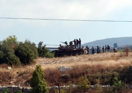 A picture released by the Syrian Arab News Agency on August 8, 2013 shows Syrian army soldiers stand next to a tank in the Latakia province