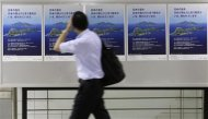 A man walks past posters of disputed islands known as Senkaku in Japan and Diaoyu in China, made by the Tokyo metropolitan government at a subway station in Tokyo September 13, 2012. REUTERS/Toru Hanai