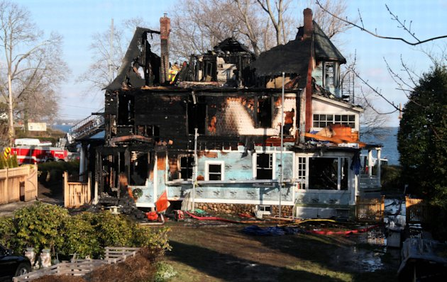 Firefighters investigate a house where an early morning fire left five people dead Sunday, Dec. 25, 2011, in Stamford, Conn. Officials said the fire, which was reported shortly before 5 a.m., killed t