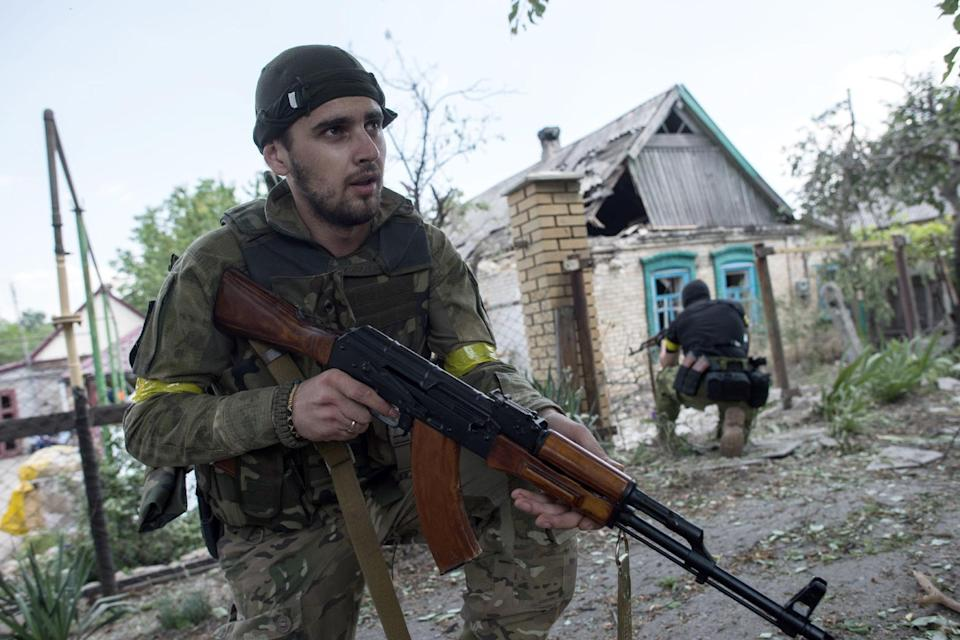 """FILE - In this June 4, 2015 file photo, Ukrainian servicemen from battalion """"Kiev1"""" guard their position near a damaged house in Marinka..."""