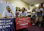 President Barack Obama, left, uses a cell phone to call supporters during a visit to a local campaign office, Monday, Oct. 1, 2012 in Henderson, Nev. Sitting with Obama is Casey Adams, center ...