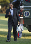 President Barack Obama gives a 'thumbs-up' as he carries bags of apples during his arrival on the South Lawn of the White House on Marine One helicopter, Saturday, Aug. 18, 2012 in Washington. Obama ...