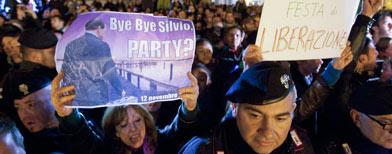 Un grupo de manifestantes italianos muestra carteles con consignas festivas tras la renuncia del primer ministro Silvio Berlusconi, en Roma, el sábado 12 de noviembre del 2011 (AP Foto/Andrew Medichini).
