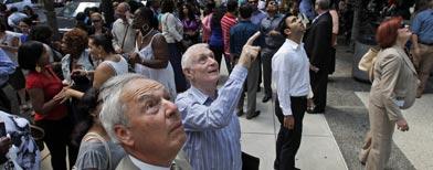 Orang-orang melihat jendela yang retak setelah evakuasi gempa di Market Street, Philadelphia, 23 Agustus 2011 (foto: AP/Alex Brandon)
