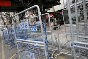 A pedestrian walks past by security barries in central…