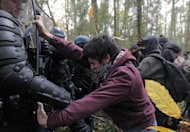 A protester confronts French riot police during the evacuation of protsetors on land that will become the new airport in Notre-Dame-des-Landes, western France Saturday Nov. 24, 2012. The protestors are opposing the building of a new airport there. In a muddy, rainy standoff starting early Friday, protesters responded to police attempts to remove them by hurling sticks, stones and gasoline bombs. For two weeks, protesters have illegally occupied the site of the planned Notre-Dame-Des-Landes airport set to start operating in 2017. (AP Photo/ Laetitia Notarianni)