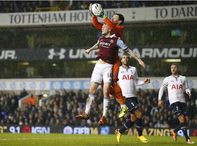 Lloris of Tottenham Hotspur beats Taylor of West Ham United to the ball during their English League Cup soccer match at White Hart Lane, London
