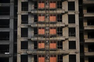 Unfinished apartments are seen at the construction…