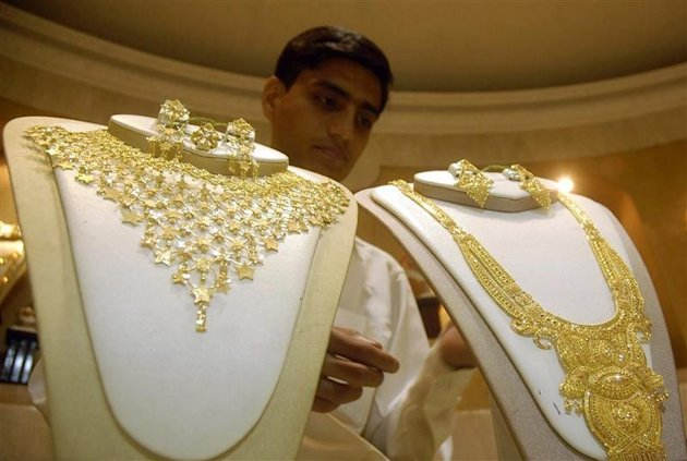 Salesman arranges gold necklaces at jewellery shop in Agartala