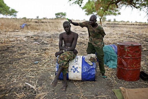 A Sudan People's Liberation Movement Army (SPLA) solider has his hair cut at a frontline position in Pana Kuach, Unity State, South Sudan on Friday, May 11, 2012. In late April, tensions between Sudan and South Sudan erupted<br /><br /><br /><br /><br /><br /><br /><br /><br />  into armed conflict along their poorly defined border. Thousands of SPLA forces have been deployed to Unity State where the two armies are at a tense stalemate around the state's expansive oil fields. Fighting between the armies lulled in early May after the U.N. Security Council ordered the countries to resume negotiations. South Sudan seceded from the Republic of Sudan in July 2011 following decades of civil war. (AP Photo/Pete Muller)