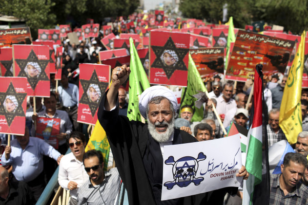 "An Iranian cleric holding an anti-Israeli placard chants slogan, while attending an annual pro-Palestinian rally marking Al-Quds (Jerusalem) Day in Tehran, Iran, Friday, Aug. 2, 2013. Ahead of his inauguration, Iran's new president, Hasan Rouhani, on Friday called Israel an ""old wound"" that should be removed, while thousands of Iranians marched in support of Muslim claims to the holy city of Jerusalem. (AP Photo/Ebrahim Noroozi)"