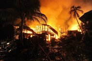 Firemen extinguish a fire engulfing houses in Sittwe, capital of the western state of Rakhine on June 15. Myanmar security forces opened fire on Rohingya Muslims, committed rape and stood by as rival mobs attacked each other during a recent wave of sectarian violence, a rights watchdog said Wednesday