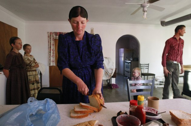 A woman from a Mennonite community slices bread for breakfast as her family members stand near her at their home in Cuauhtemoc November 9, 2012. More than a century after Mennonite farmers left Russia for North America in search of new lands and religious freedom, hundreds of their descendants in Mexico are thinking about completing the circle. Shortage of farmland, drought and conflict with rivals have made some Mennonites in northern Mexico wonder if the best way of providing for their families is to go back to the plains of eastern Europe their ancestors left in the 19th century.  Picture taken November 9, 2012. To match Feature MEXICO-MENNONITES/     REUTERS/Jose Luis Gonzalez (MEXICO - Tags: FOOD SOCIETY RELIGION)