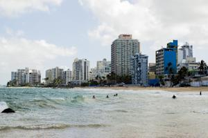 Vacant buildings dot the coast in the upscale Condado…