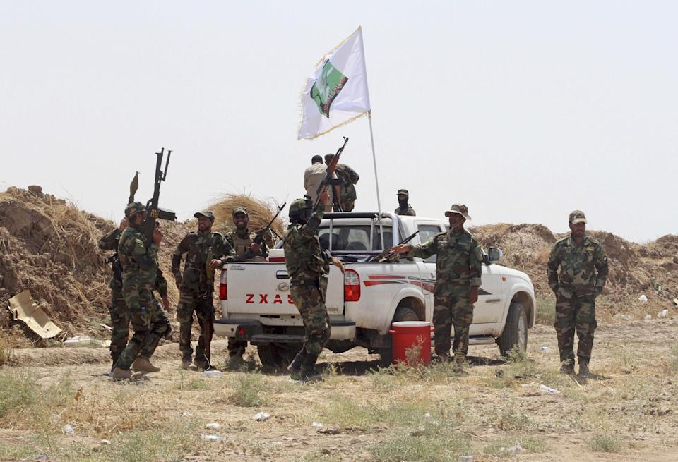 FILE - In this  Sunday, Aug. 31, 2014, file photo, Iraqi security forces and Shiite militiamen chant anti-terrorism slogans after breaking the siege...