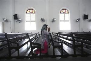 A woman prays inside the church of Our Lady of Lourdes…