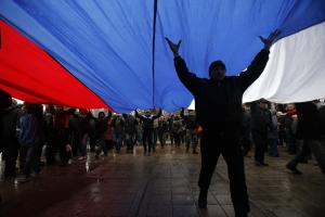 Pro-Russian demonstrators march with a huge Russian …