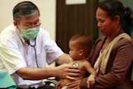 "A doctor checks a child at Kantha Bopha children's hospital in Phnom Penh. Medical experts are scrambling to respond to what the Cambodian health ministry and World Health Organization have labelled an ""undiagnosed syndrome"" that has claimed the lives of at least 56 boys and girls, mostly toddlers, since April"