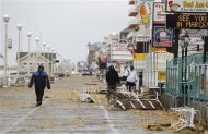 Residents walk by debris on the boardwalk after Hurricane Sandy in Ocean City, Maryland October 30, 2012. Millions of people across the eastern U.S. awoke to scenes of destruction wrought by monster storm Sandy, which knocked out power to huge swathes of the densely populated region. REUTERS/Kevin Lamarque