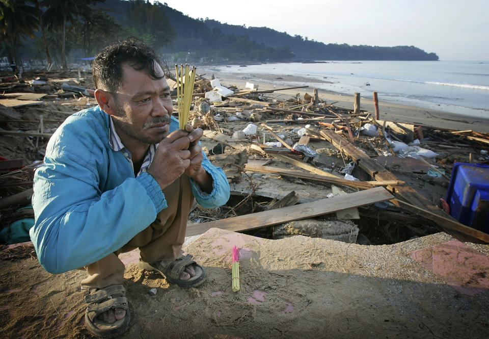 FILE - In this Dec. 29, 2004 file photo, Kusol Wetchakul offers prayers for the soul of his sister , at dawn along the beach near Khao Lak, Thailand. ...
