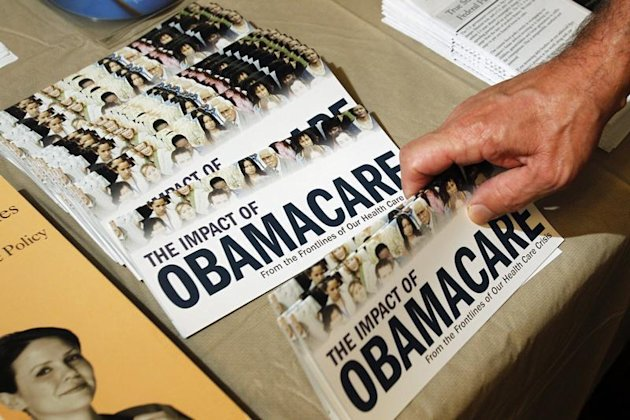 """A Tea Party member reaches for a pamphlet titled """"The Impact of Obamacare"""", at a """"Food for Free Minds Tea Party Rally"""" in Littleton, New Hampshire in this October 27, 2012 file photo. REUTERS/Jessica Rinaldi//Files"""