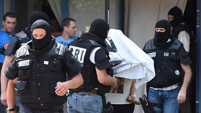Special forces of France's Research and Intervention Brigades (BRI) escort an unidentified woman and a child as they leave the building housing the apartment of a man suspected of carrying out an attack in Saint-Priest near Lyon on June 26, 2015