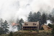 Flames erupt near a house in Colorado's High Park Fire, about 15 miles (24 km) northwest of Fort Collins June 11, 2012. REUTERS/Rick Wilking