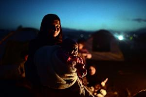 A woman holds her crying baby at a makeshift camp by…
